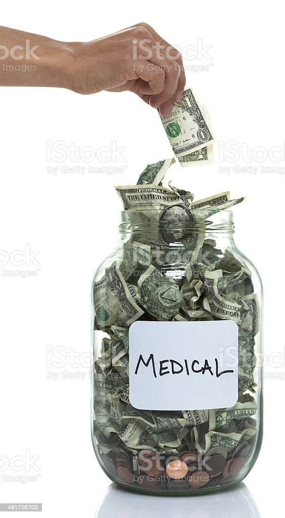 Hand putting money into savings jar with white medical label stock photo