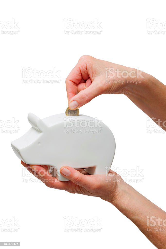 hand putting one coin in a piggy bank royalty-free stock photo