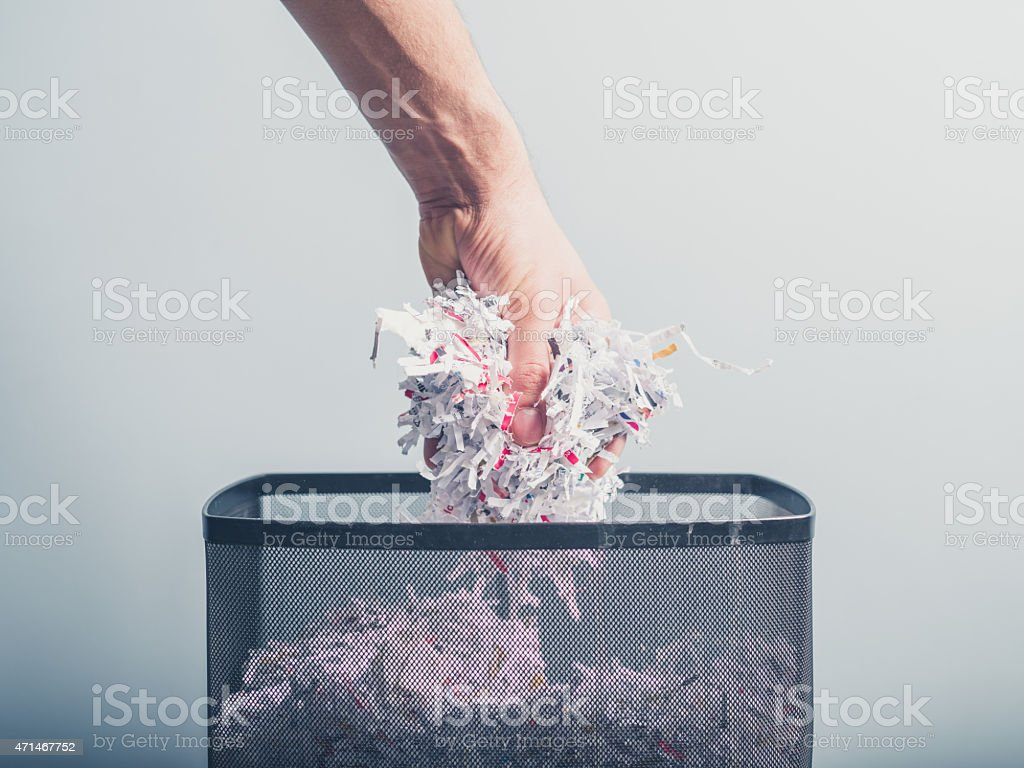 Hand putting shredded paper in basket stock photo