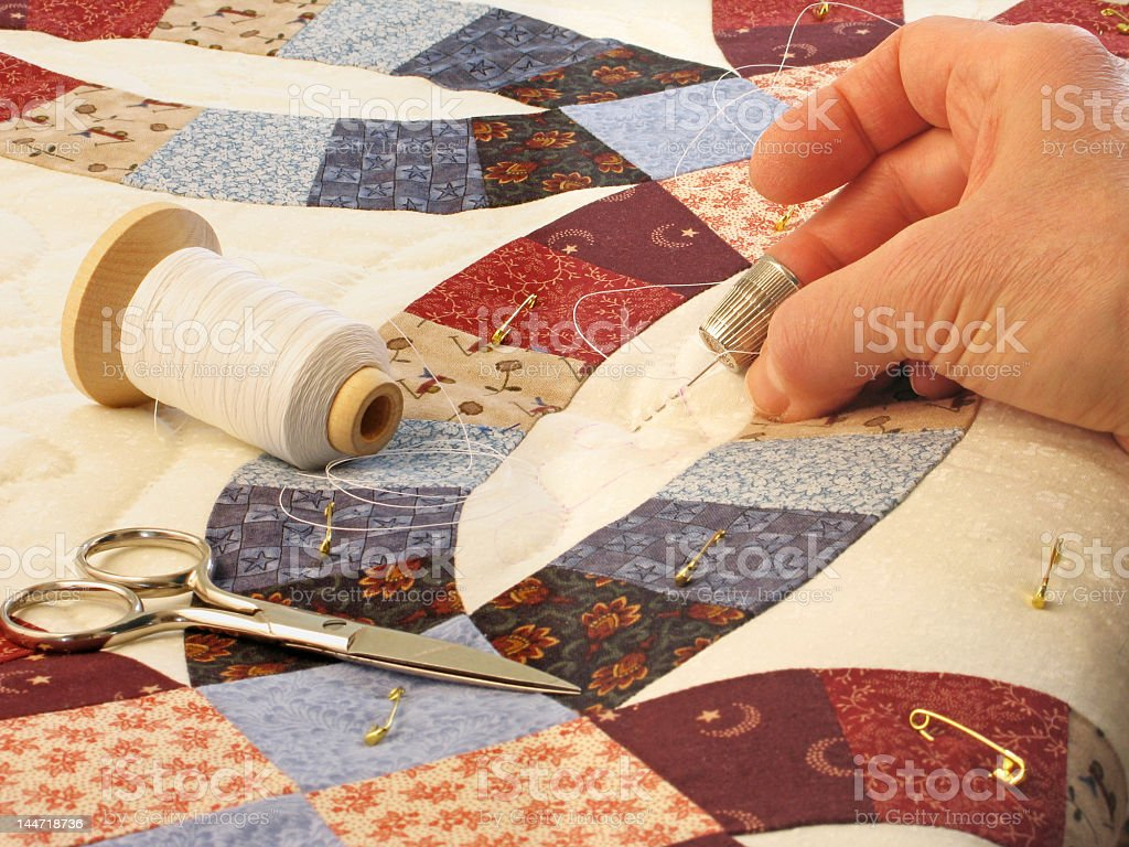 Hand quilting of double wedding ring patterned quilt stock photo