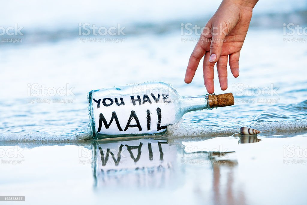 Hand reaches for You have Mail message in bottle royalty-free stock photo