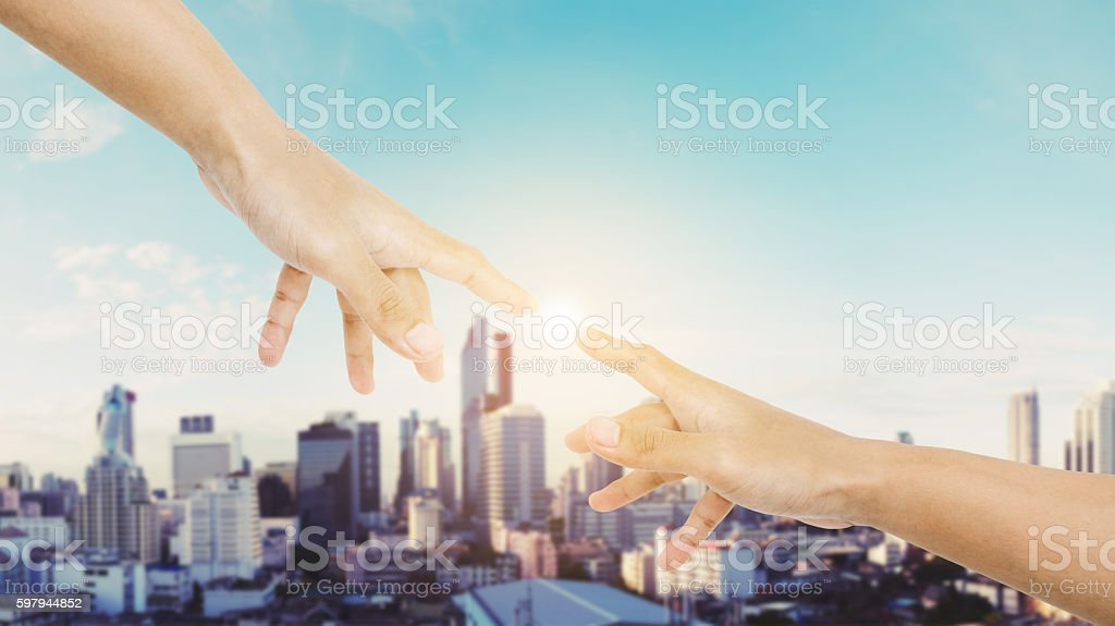 Hand reaching finger together with shine bright light stock photo
