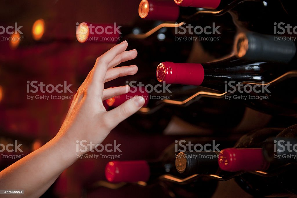hand reaching for bottle of wine in a wine cellar royalty-free stock photo