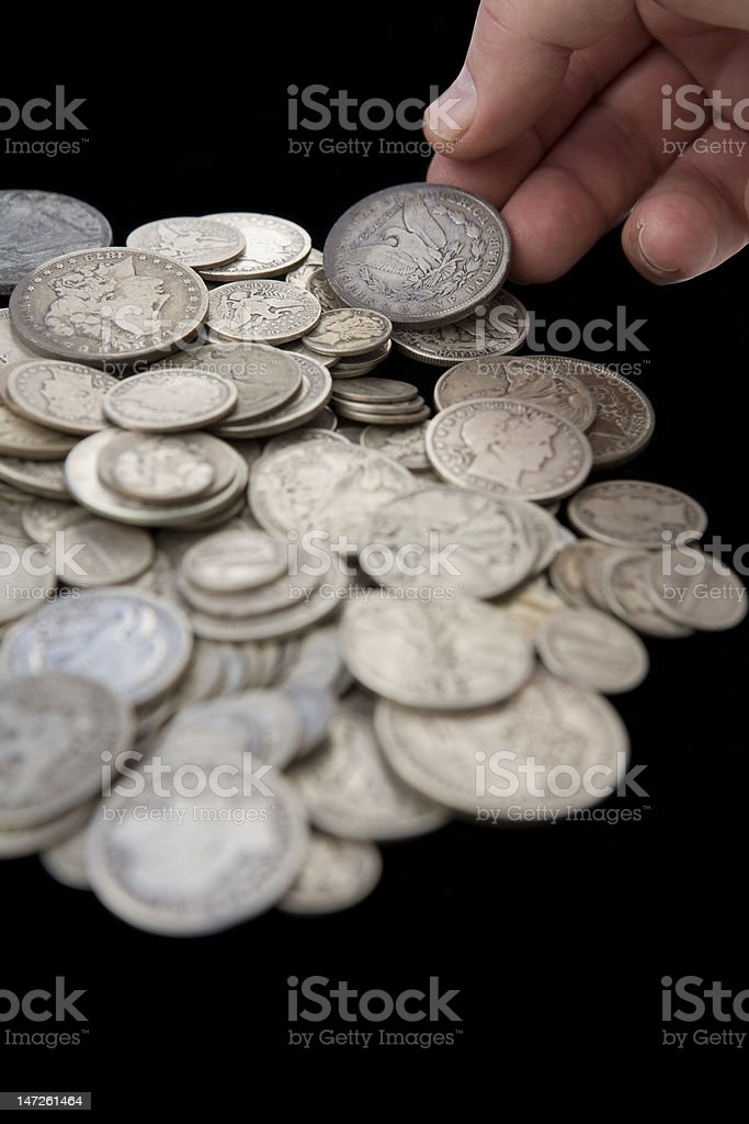 Hand Reaching for Coins from Savings – Vertical royalty-free stock photo