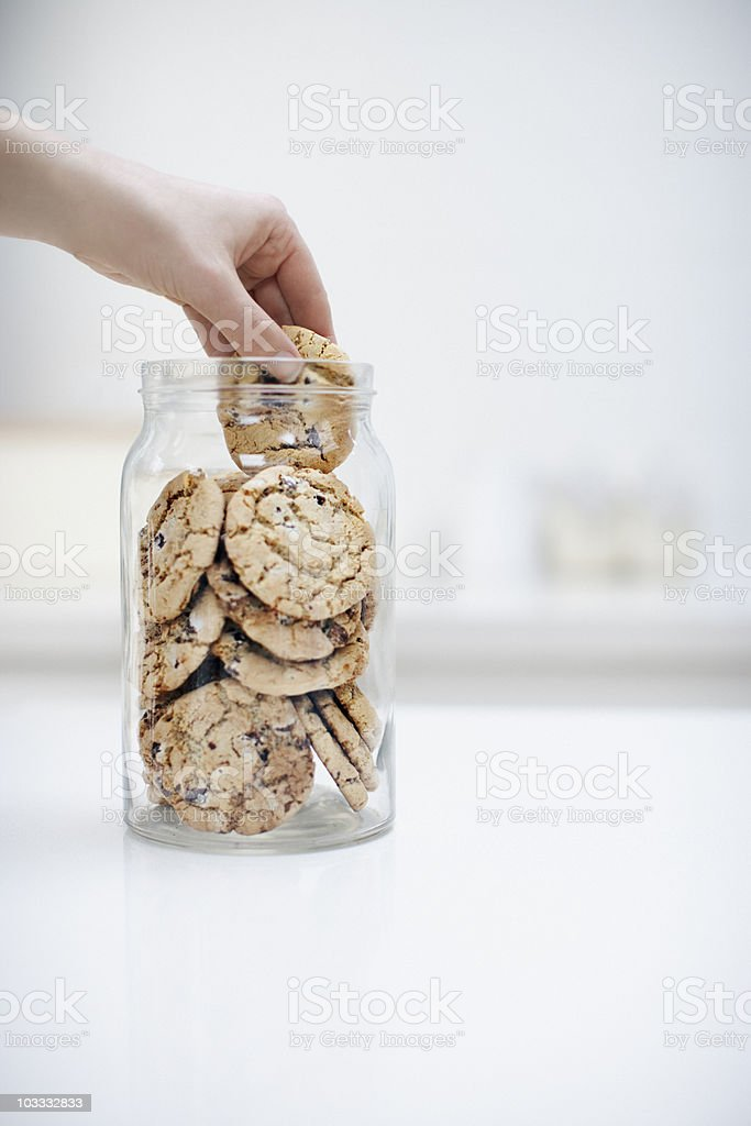 Hand reaching for cookie in jar royalty-free stock photo