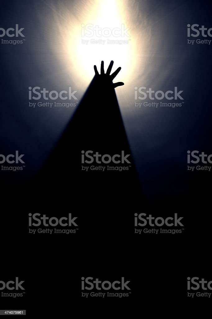 Hand reaching for the light stock photo