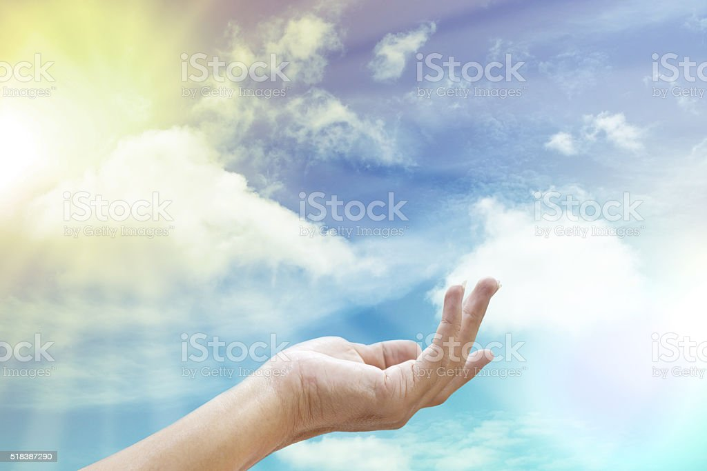 Hand reaching for the sun and sky stock photo
