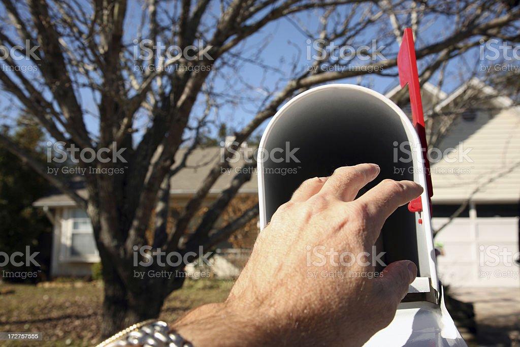 Hand reaching inside mailbox stock photo