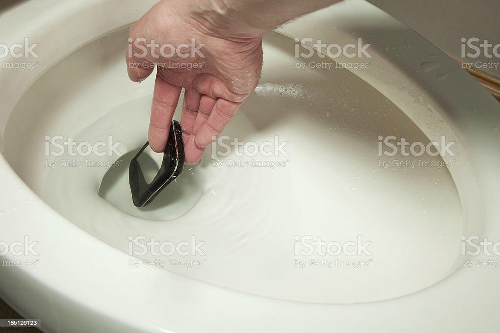 Hand Reaching into Toilet to Retrieve a Mobile Phone stock photo