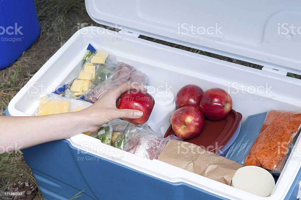 Hand reaching out for an apple out of a cooler stock photo