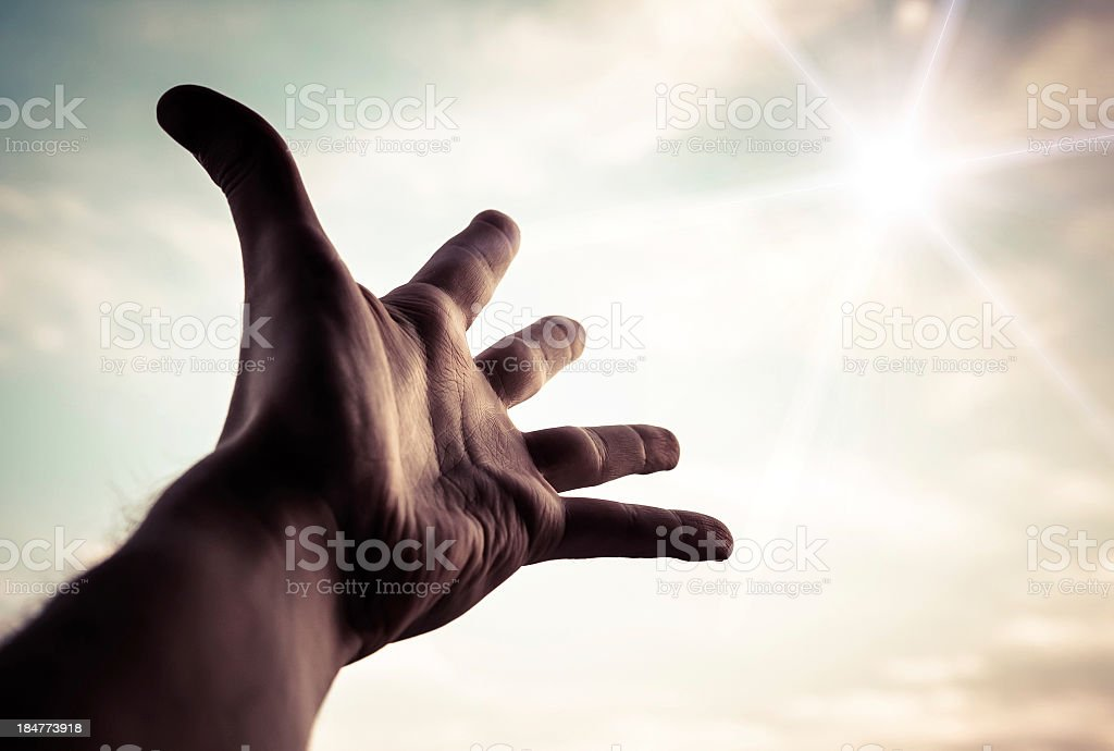 Hand reaching to towards sky. stock photo