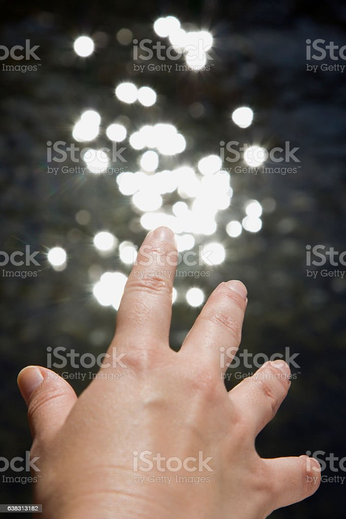 Hand reaching towards reflections of sunlight in water stock photo