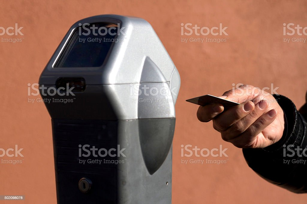 Hand Ready to Swipe Card at Parking Meter (Close-Up) stock photo