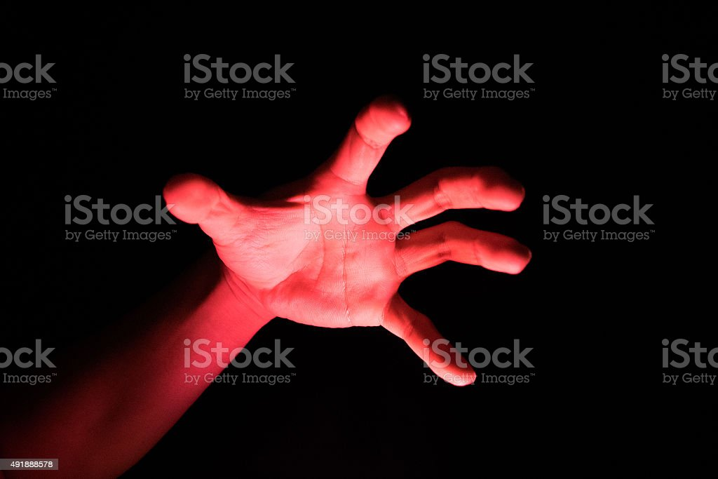 Hand Reflective red light in the dark background for scary stock photo
