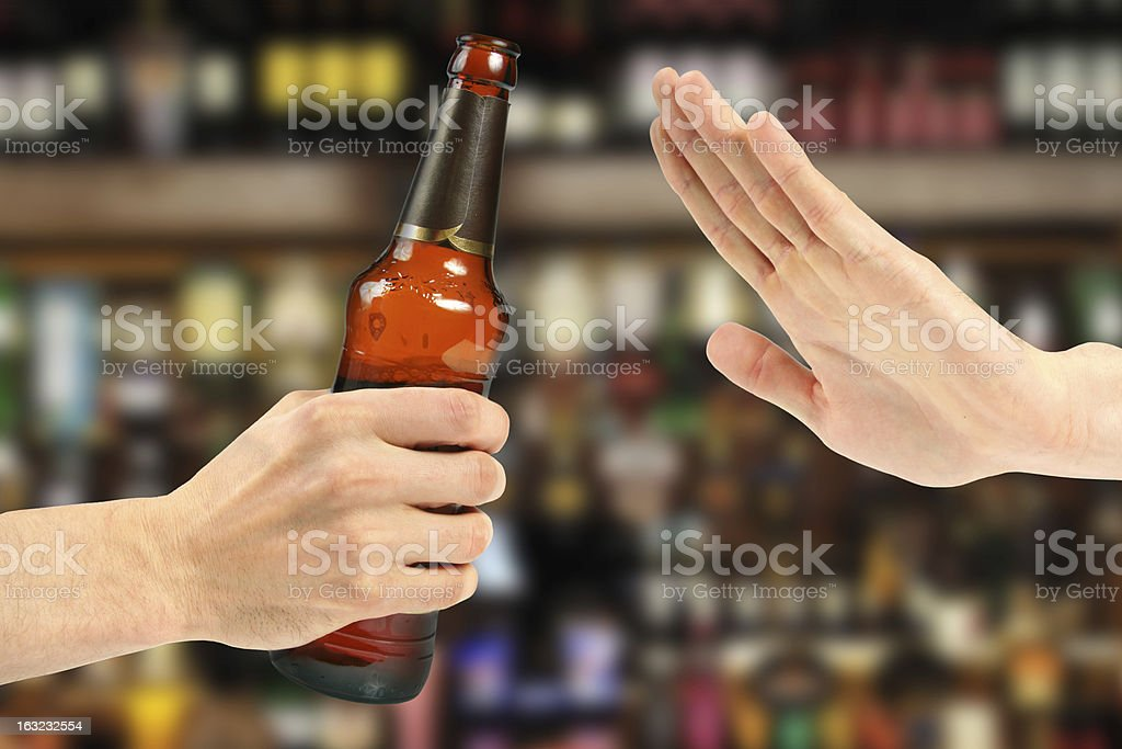 Hand rejecting a bottle of beer stock photo