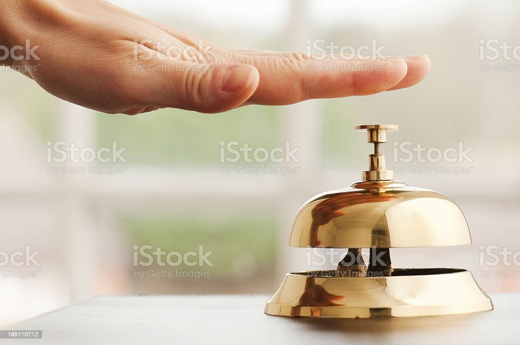 Hand ringing service bell on desk beside window stock photo