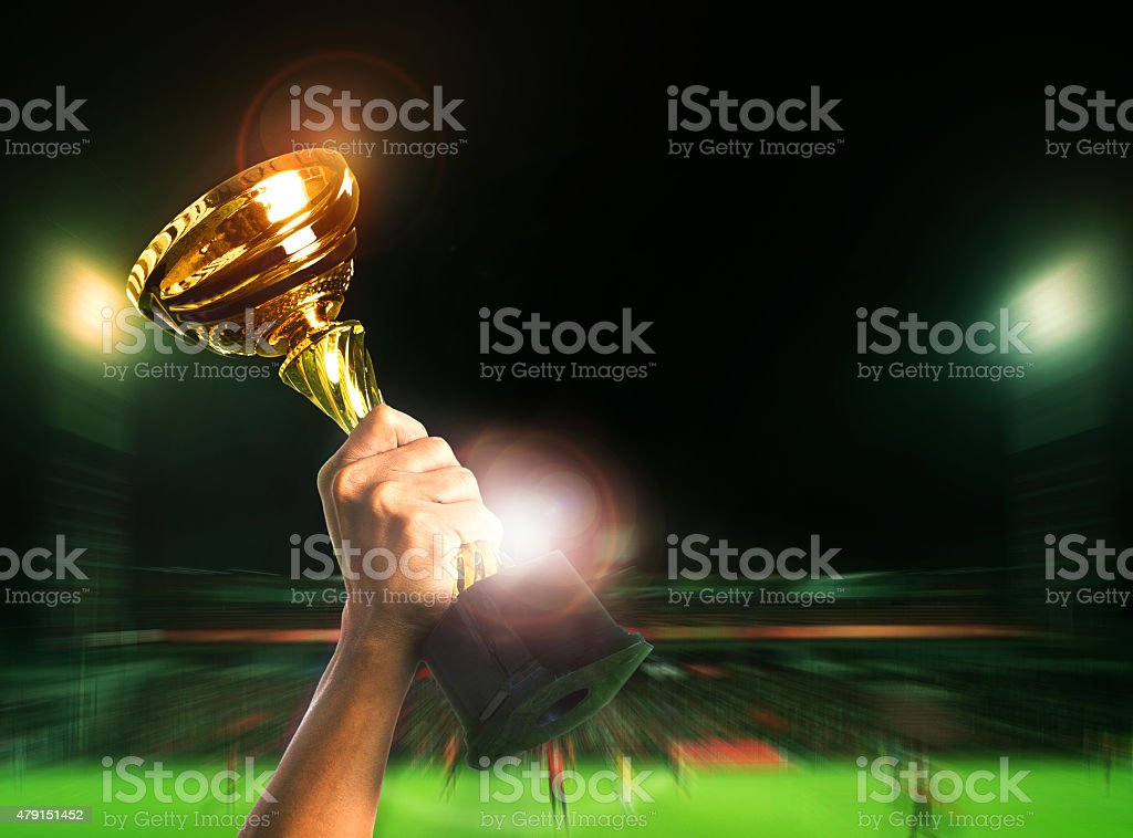 hand rising soccer football championship cup stock photo