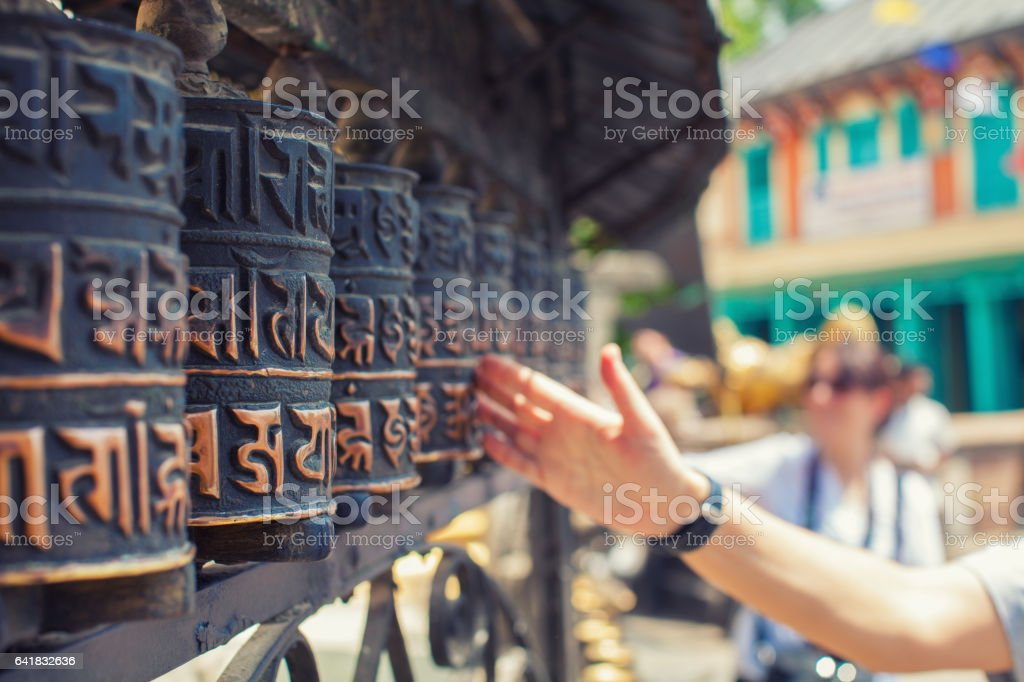 Hand rolling prayer wheels in Buddhist temple stock photo