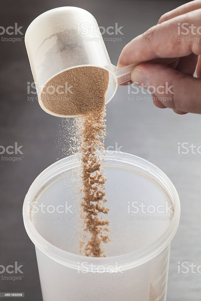 Hand scooping chocolate whey isolate protein stock photo