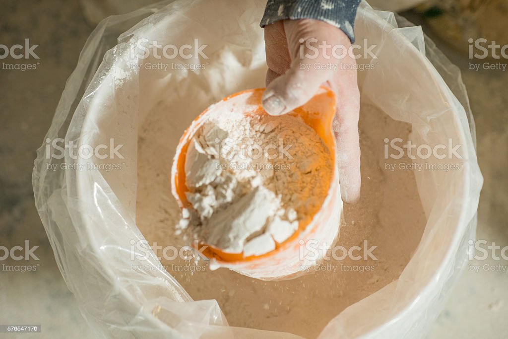 Hand Scooping Powder Plaster with Plastic Dipper from Large Buck stock photo