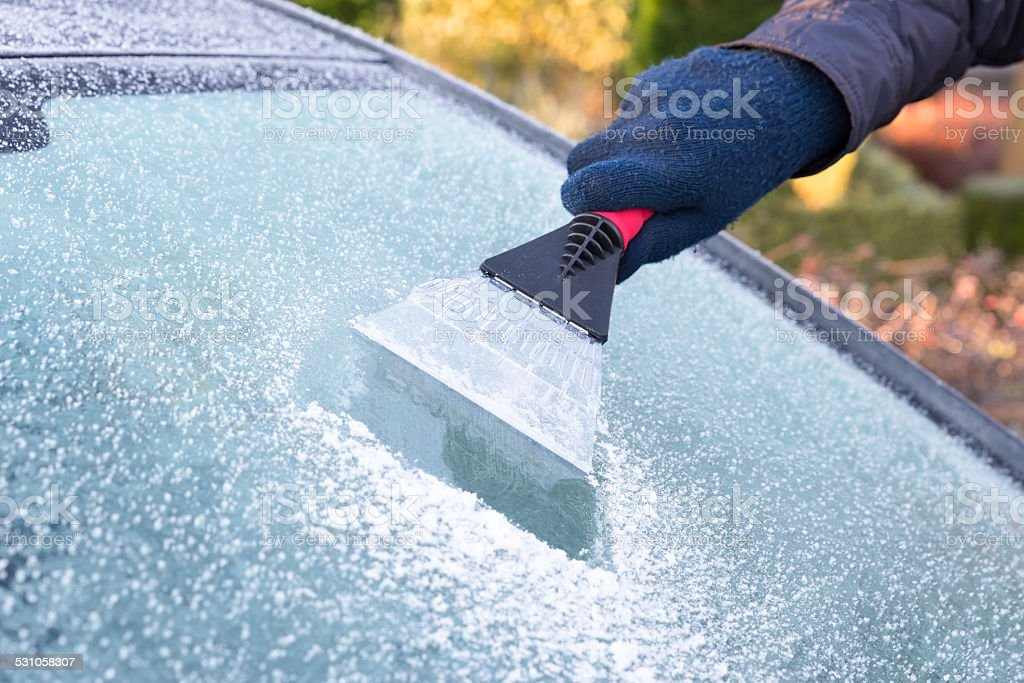 Hand scratching ice from car window stock photo