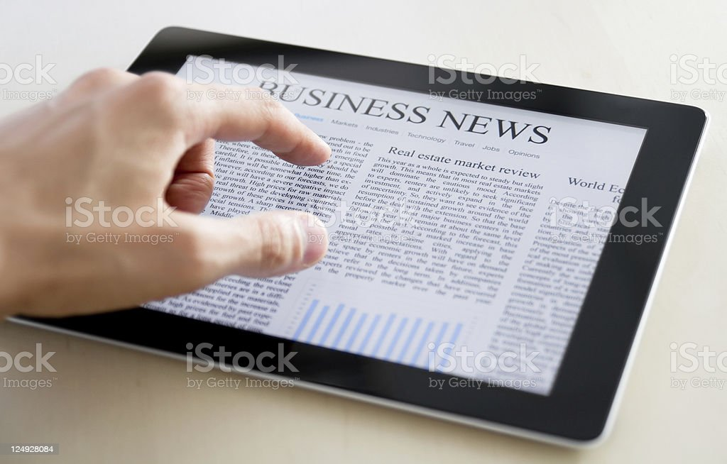 Hand scrolling through business news on PC tablet stock photo
