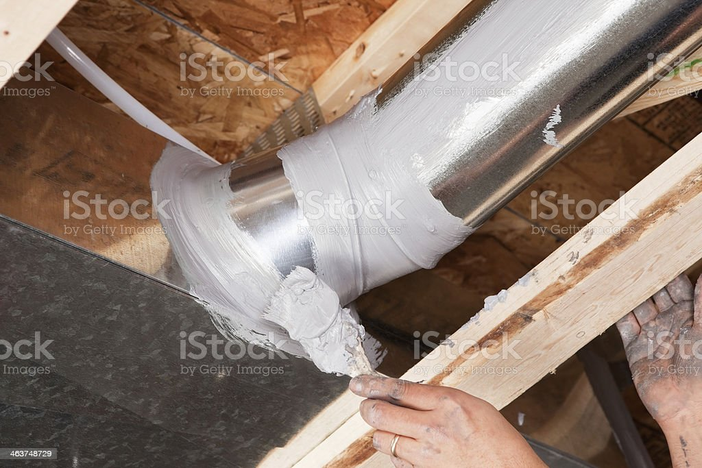 Hand Sealing House Air Duct Joint with Caulk stock photo
