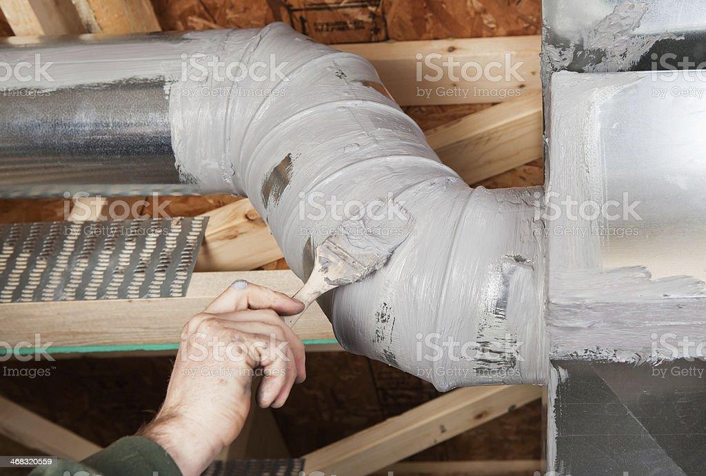 Hand Sealing House Air Duct Seam with Caulk stock photo