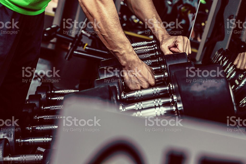 Hand Selects Weights From Rack in Gym stock photo