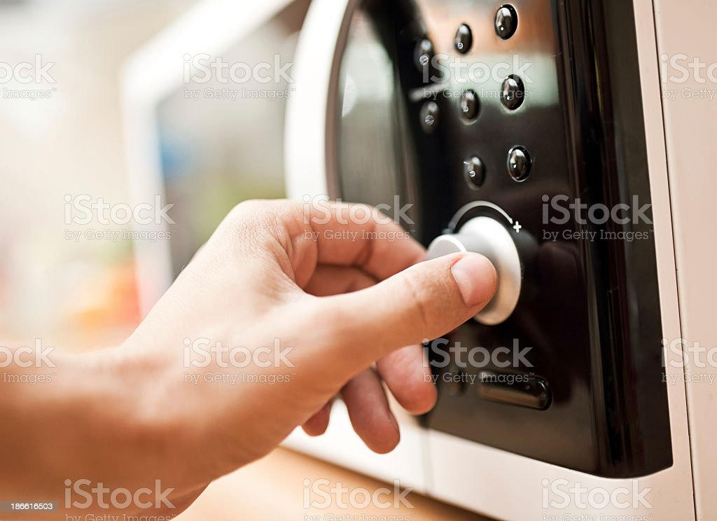 Hand setting the controls on a microwave oven stock photo