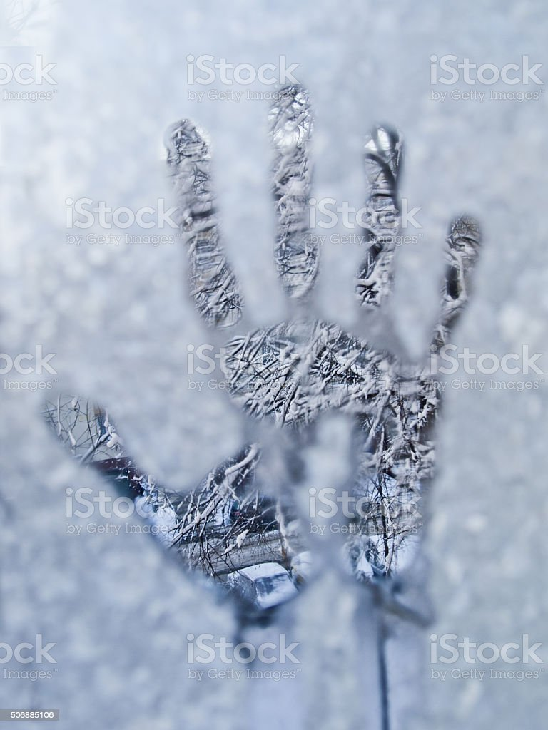 Hand shape on window glass in a frosty winter day stock photo