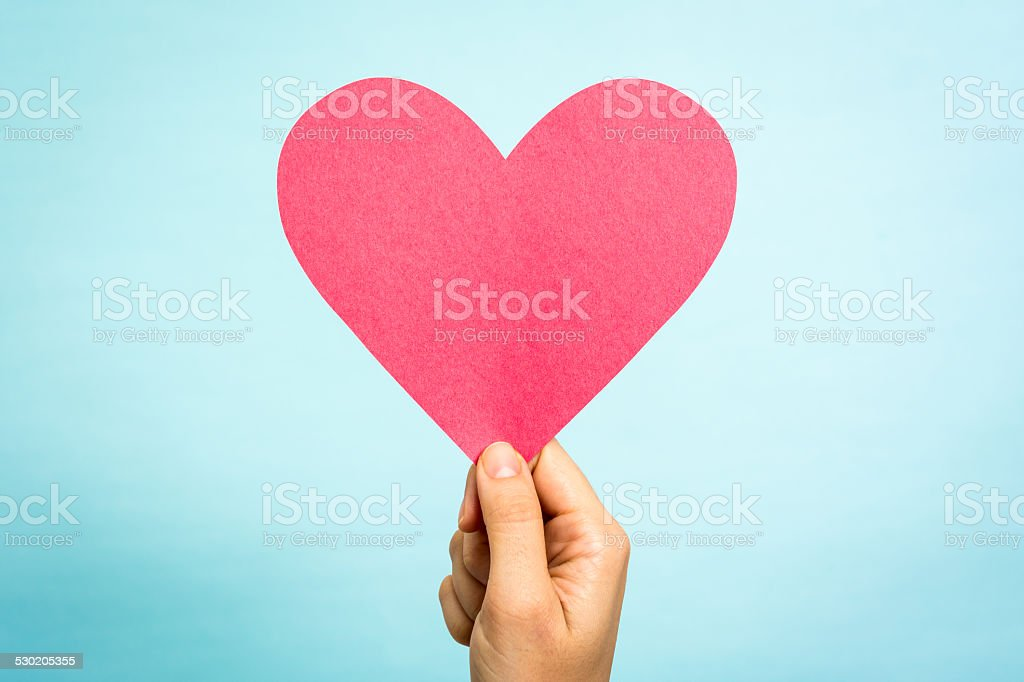 Hand showing big red pink heart love symbol blue background stock photo