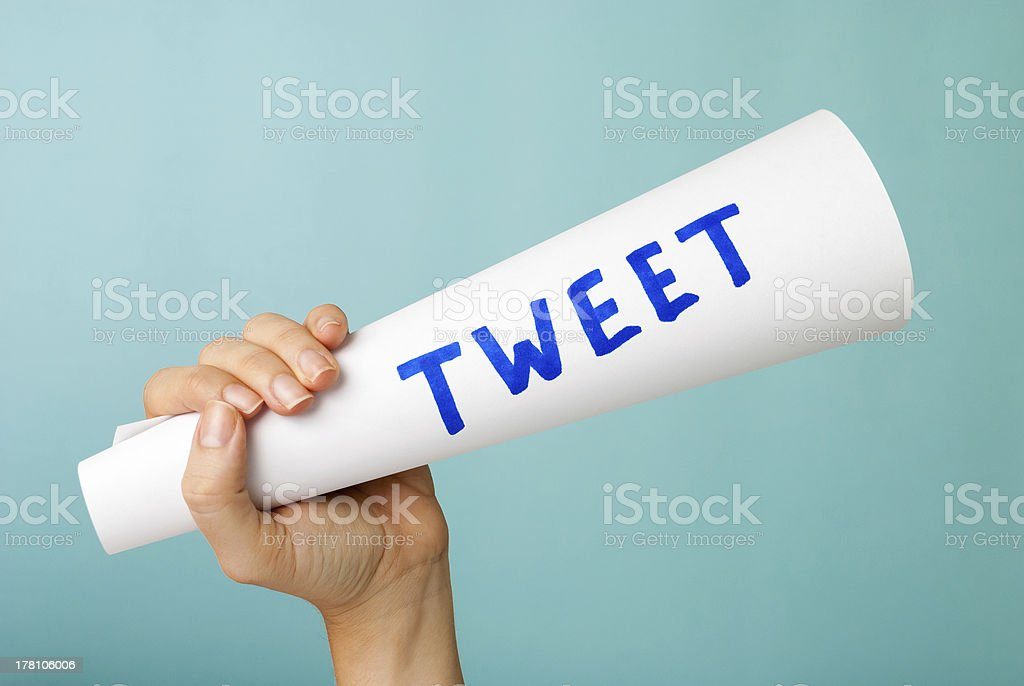 Hand showing blue tweet word handwritten, megaphone. Social media concept. stock photo