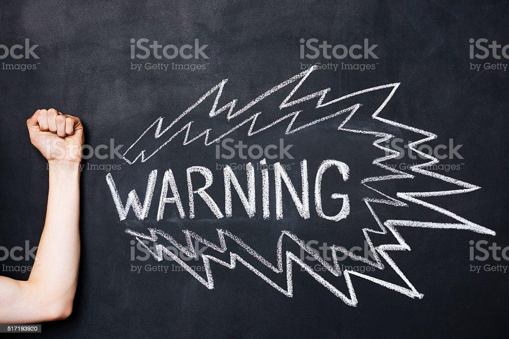 Hand showing fist near warning drawn on blackboard stock photo