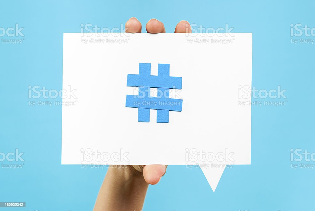 Hand showing internet social media trend topic hashtag speech bubble stock photo