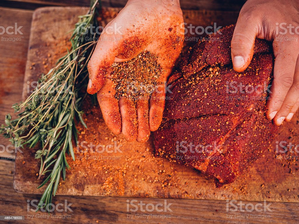 Hand showing spicy seasoning with a piece of raw pork stock photo