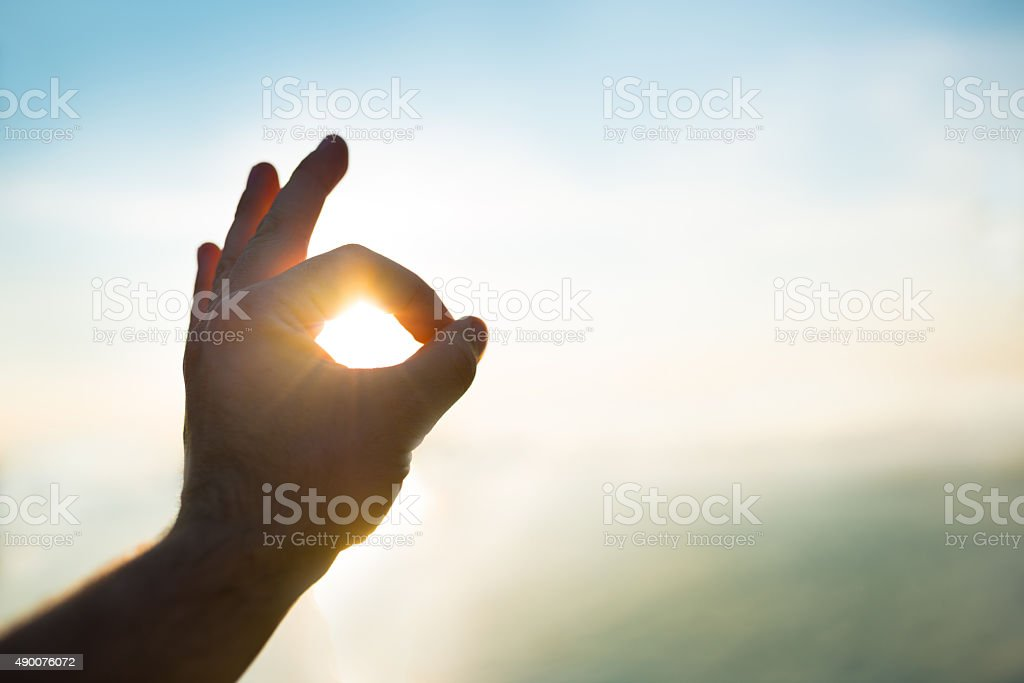 OK hand sign against sun stock photo