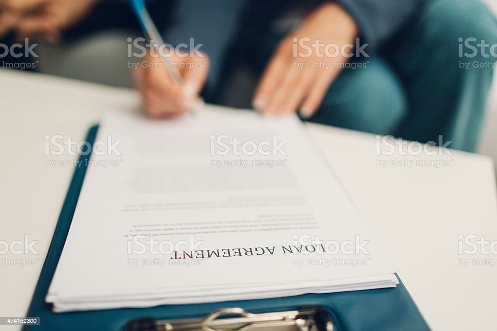 Hand Signing Loan Agreement Document. stock photo
