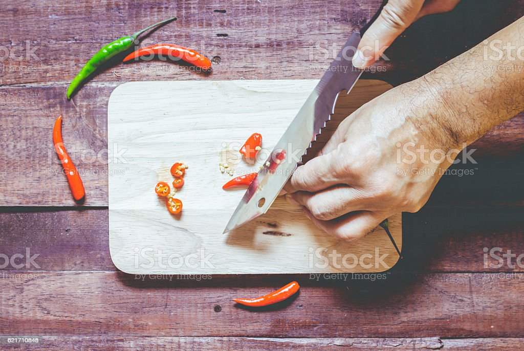 Hand slicing chili pepper with Knife on chopping board  stock photo