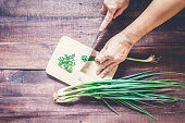 Hand slicing green onions with Knife on chopping board
