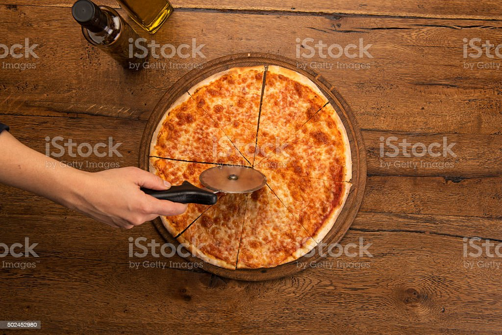 hand slicing margherita pizza with a pizza knife stock photo