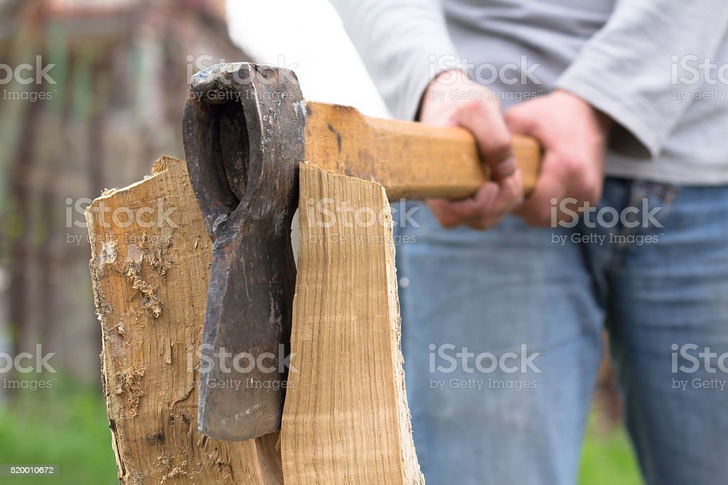Hand slicing wood by axe stock photo