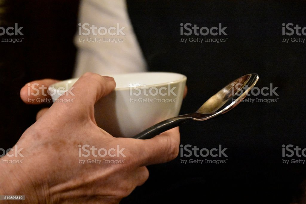 Hand, small bowl and spoon stock photo