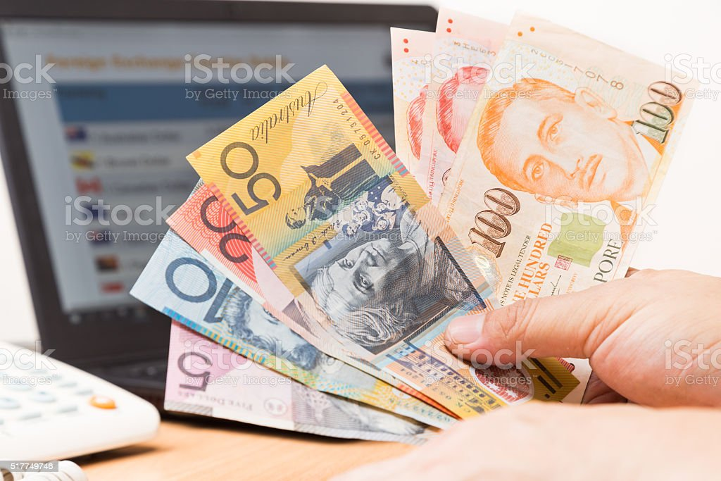 Hand sorting Australian Dollar and Singapore Dollar with computer background stock photo