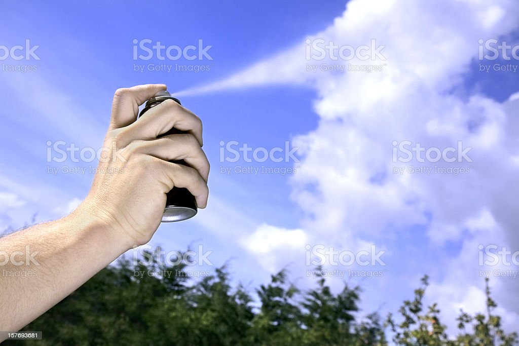 Hand spraying aerosol can into sky, forming chemical trails stock photo
