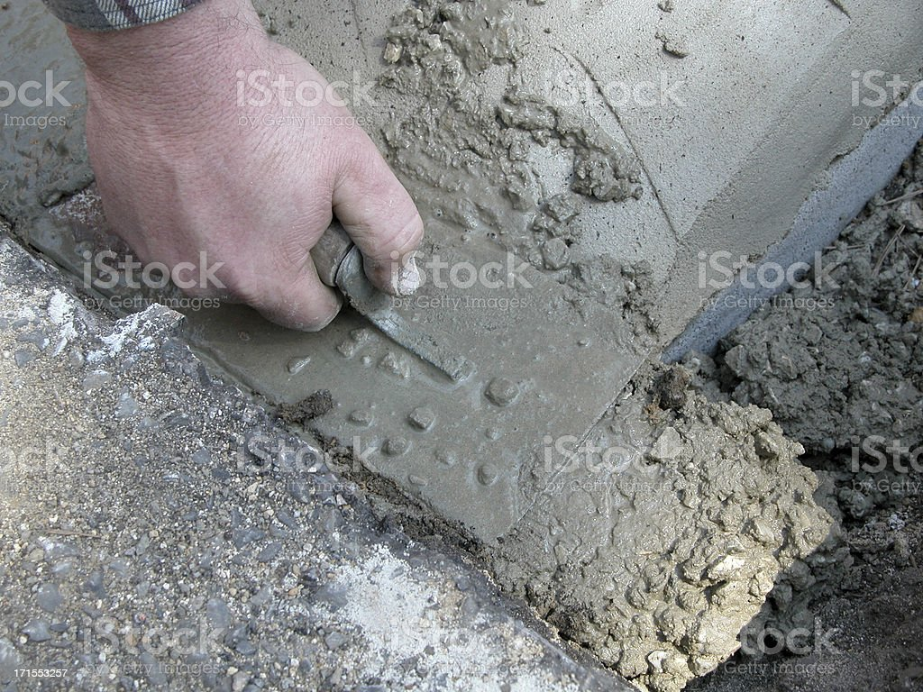 Hand Spreading Concrete with Cement Trowel royalty-free stock photo