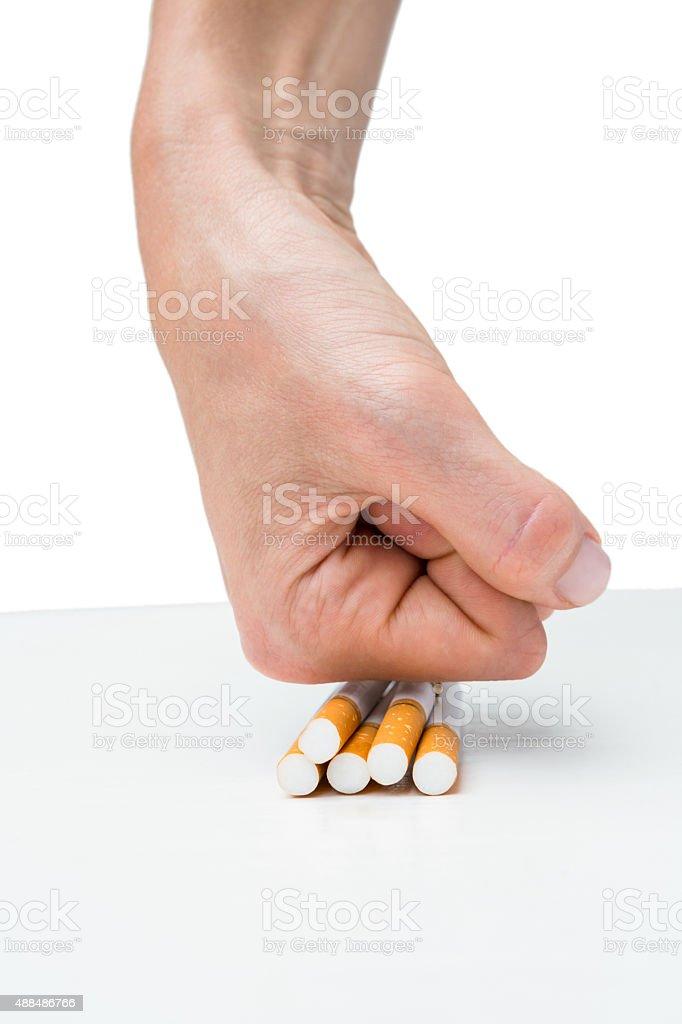 Hand squashing batch of cigarettes stock photo