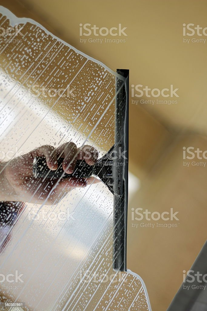 Hand squeegeeing a window with soap clean stock photo