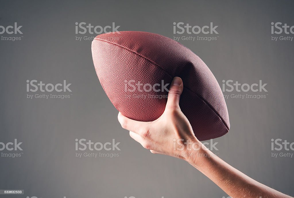 Hand Squeezing a Half Deflated Football stock photo