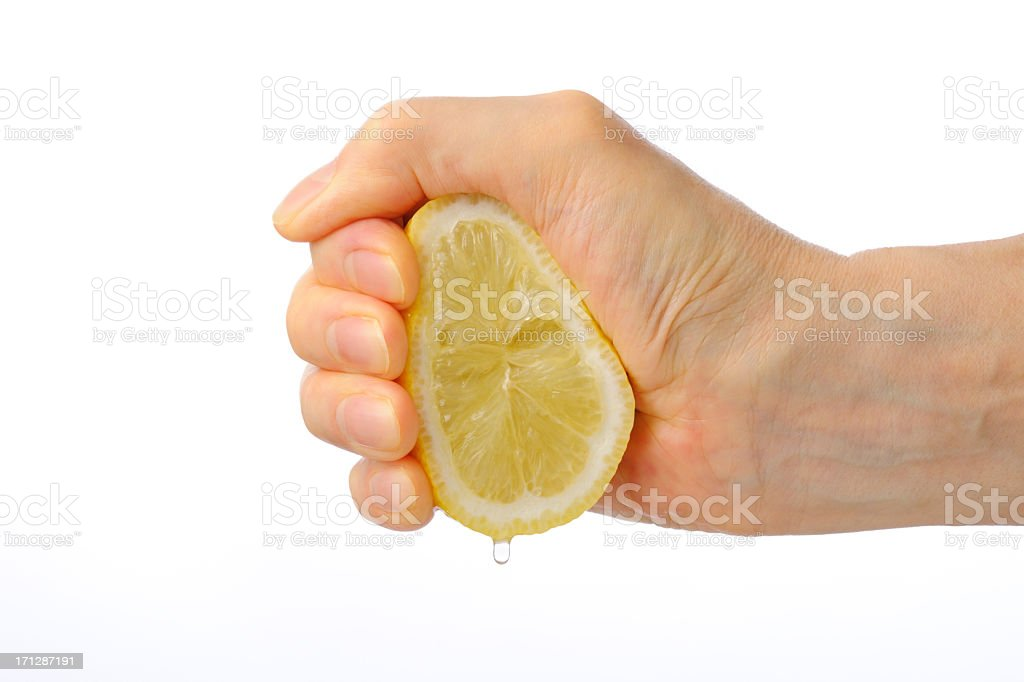 Hand squeezing a lemon against white background stock photo